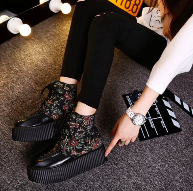 Model wears black leggings, a button down blouse, and shiny black creepers with floral detailing on the side