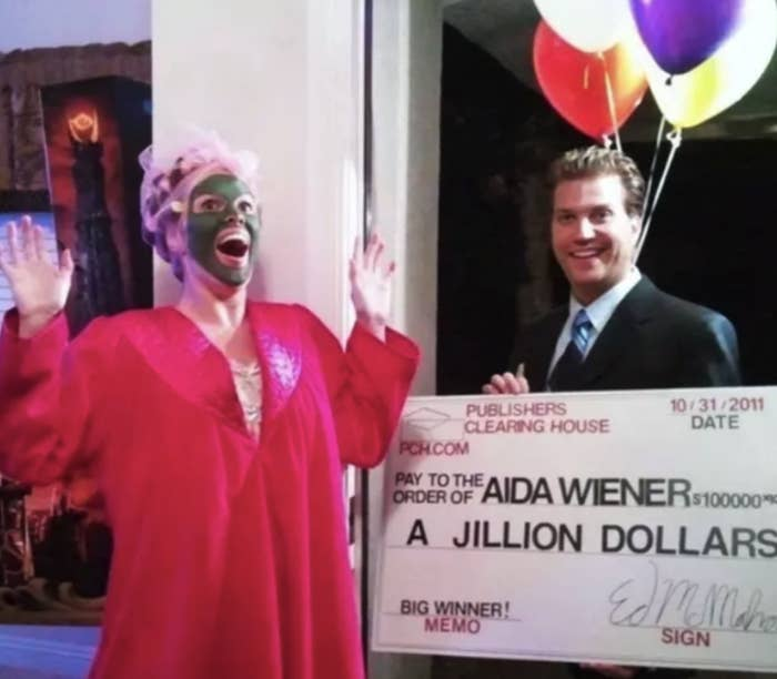 A woman dressed as a Publishers Clearing House winner (robe and face mask and all), and a spokesperson with a giant check
