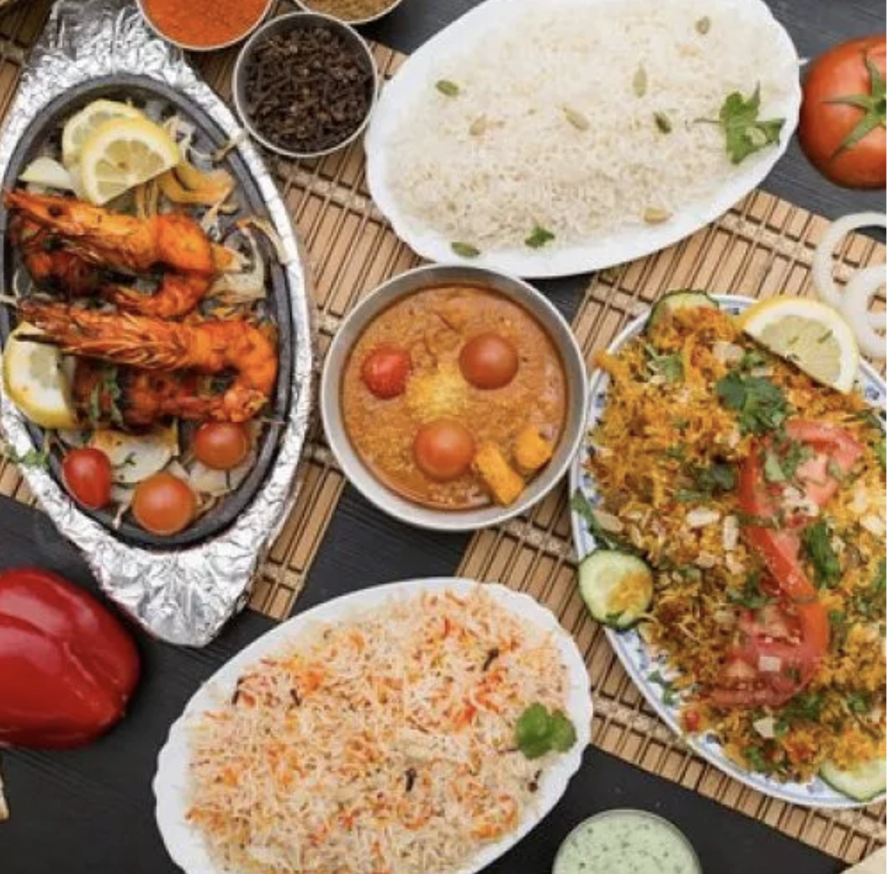 An overhead view of rice, seafood, and meat dishes