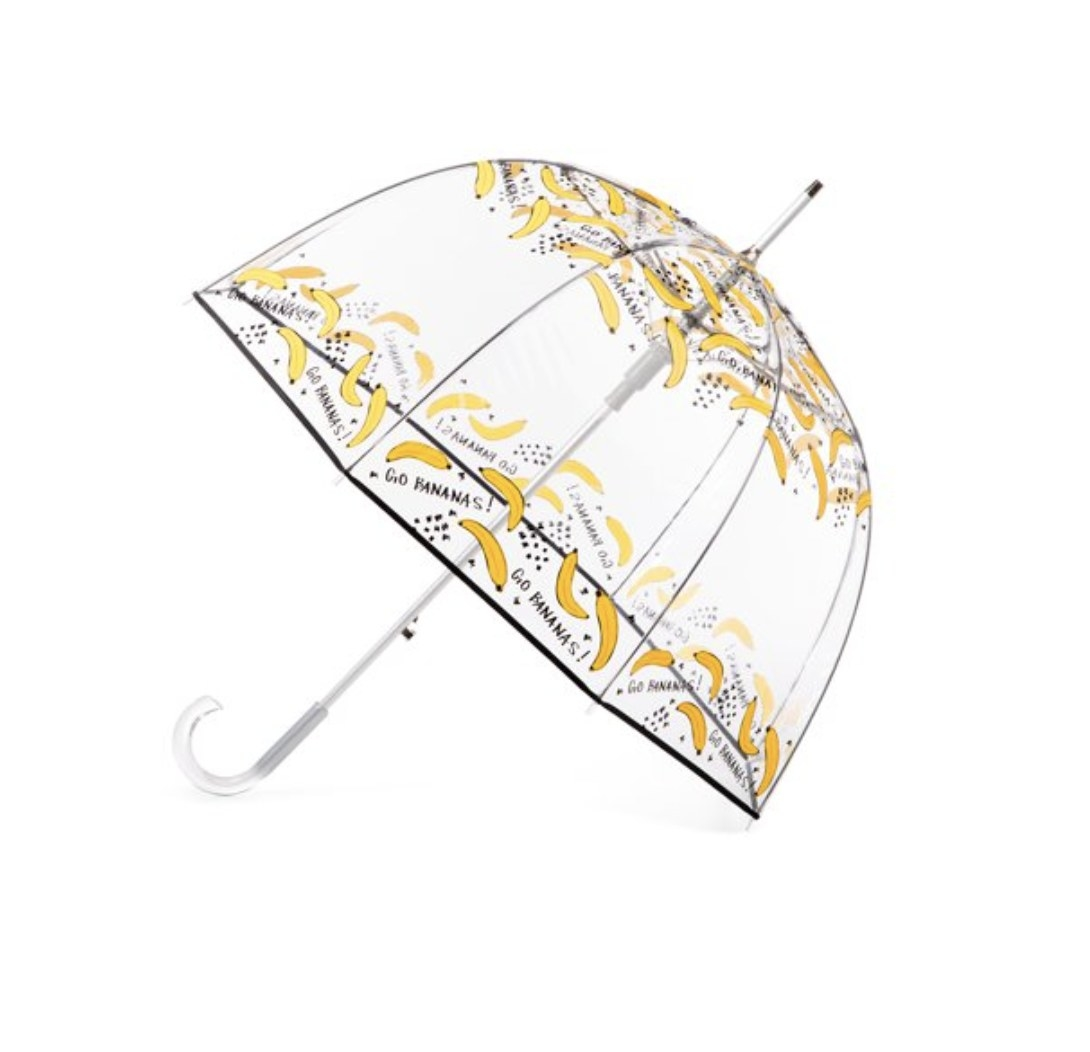 A clear bubble umbrella with bananas printed around it with the words Go Bananas
