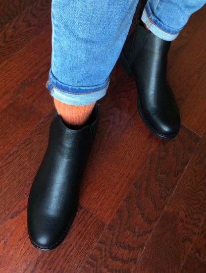 Reviewer wears black Chelsea-style boots with orange socks and light blue jeans
