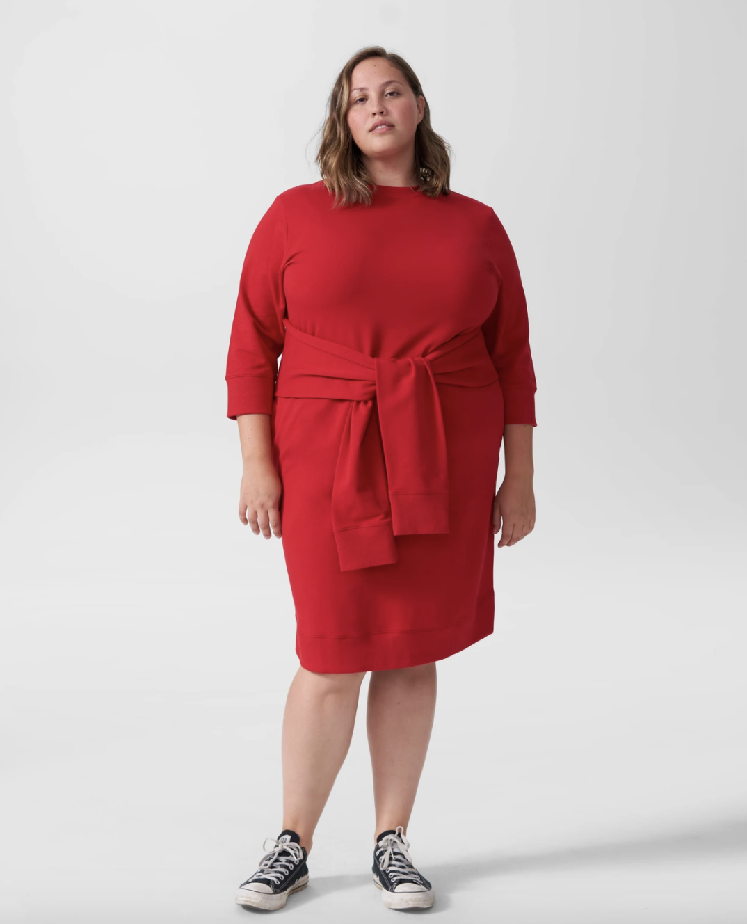 model wearing the dress in red, which has two attached sleeves tied around the waist