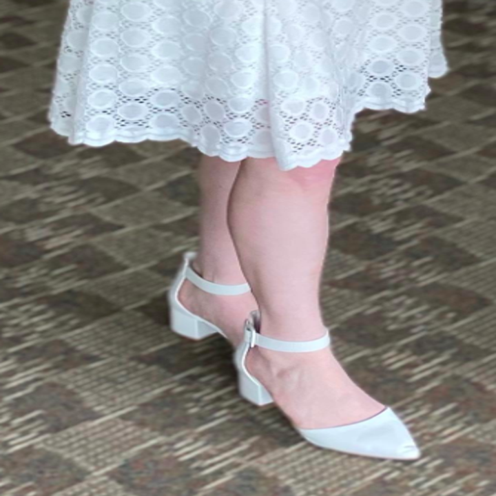 Reviewer wears the low-heel ankle-strap pump in a white shade with a white embroidered dress