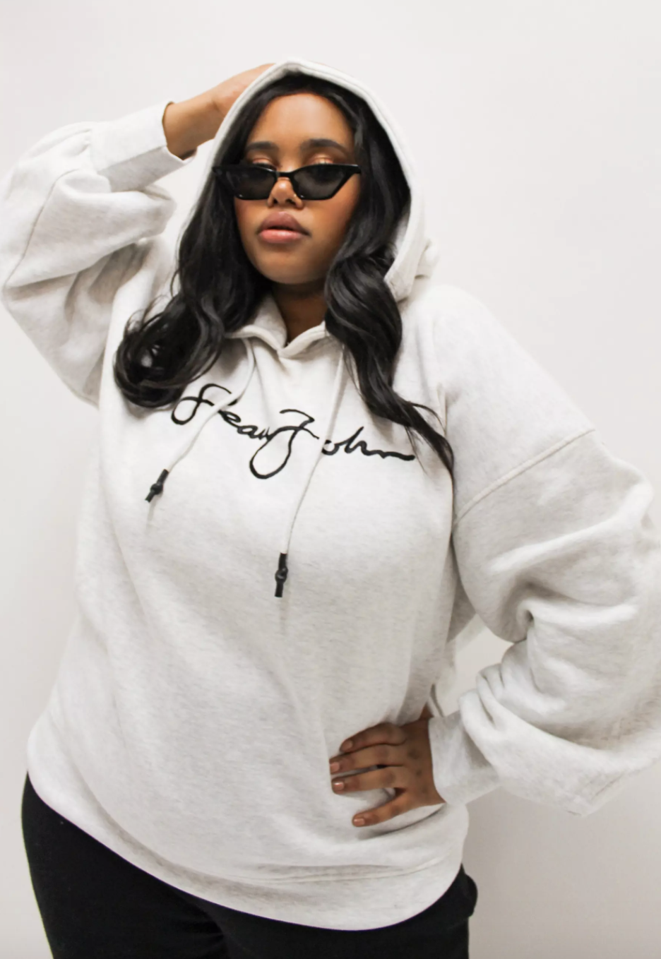 model wearing a gray hoodie that says sean john on the front