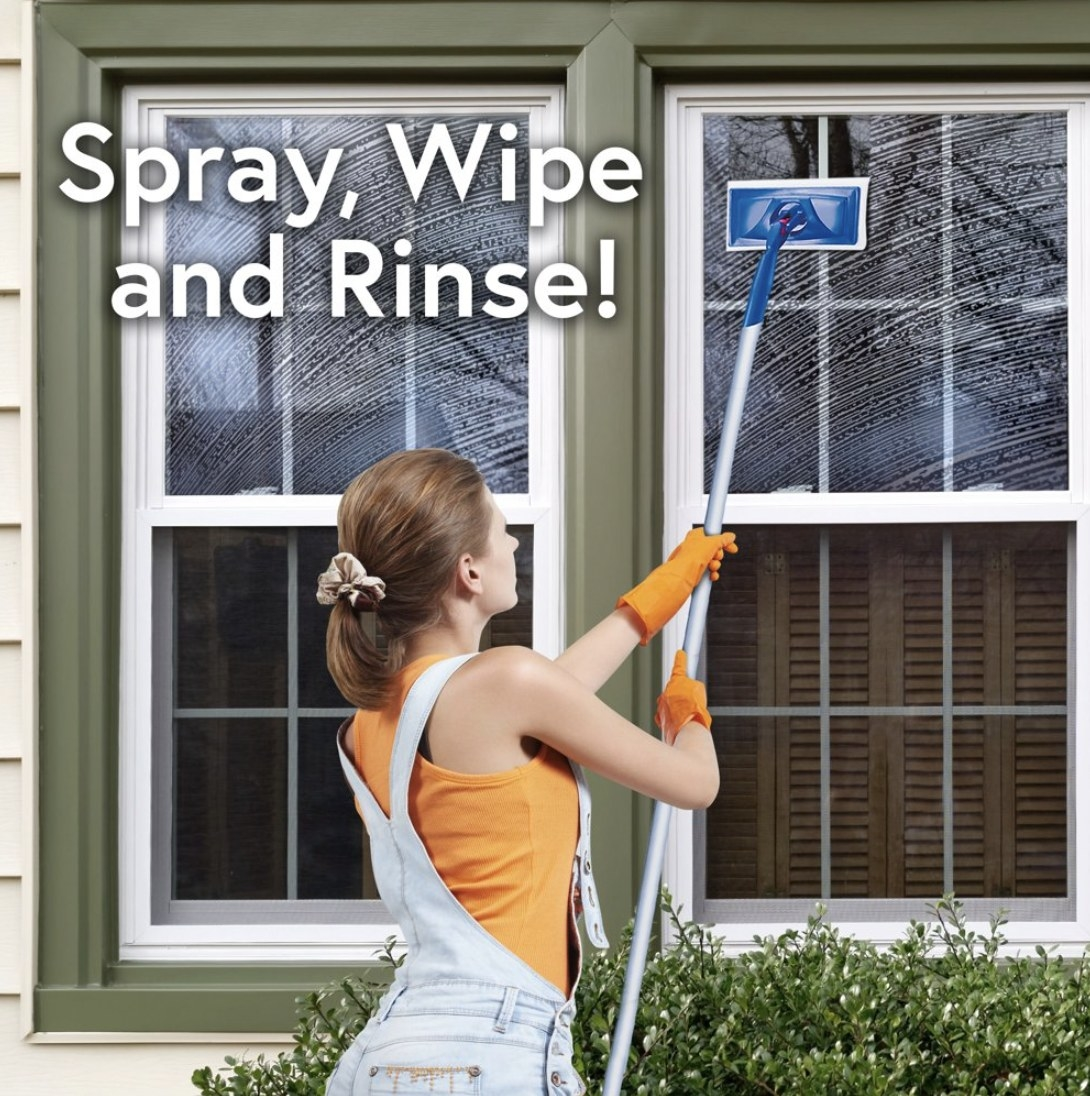 Model is outside of a home wiping windows clean with an expandable cleaning tool