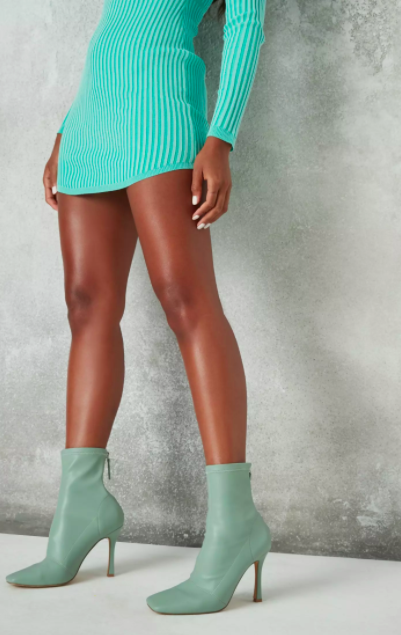 Model wears mint stiletto boots with a teal bodycon dress