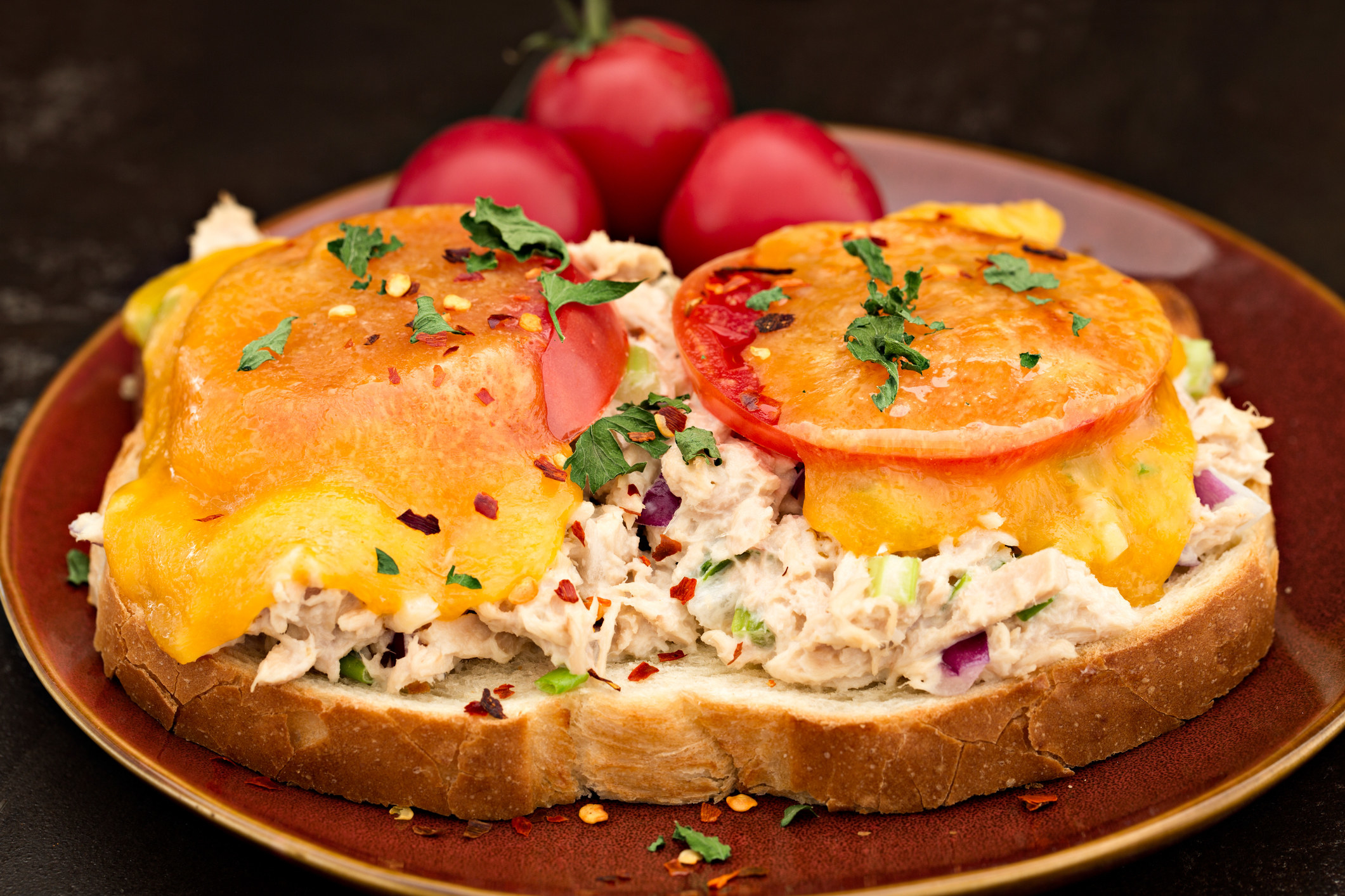 A tuna melt topped with cheese and sliced tomatoes.