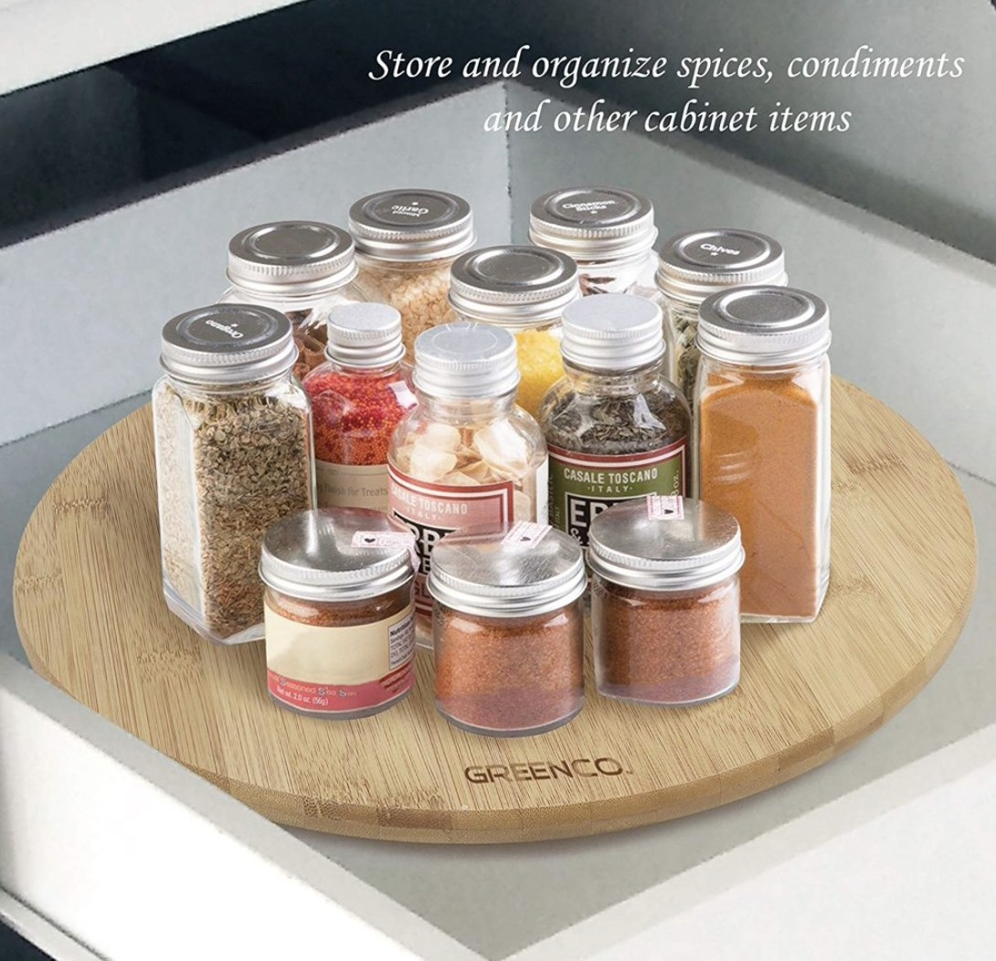A light wooden turntable lazy Susan with various spices on top in a pull out drawer