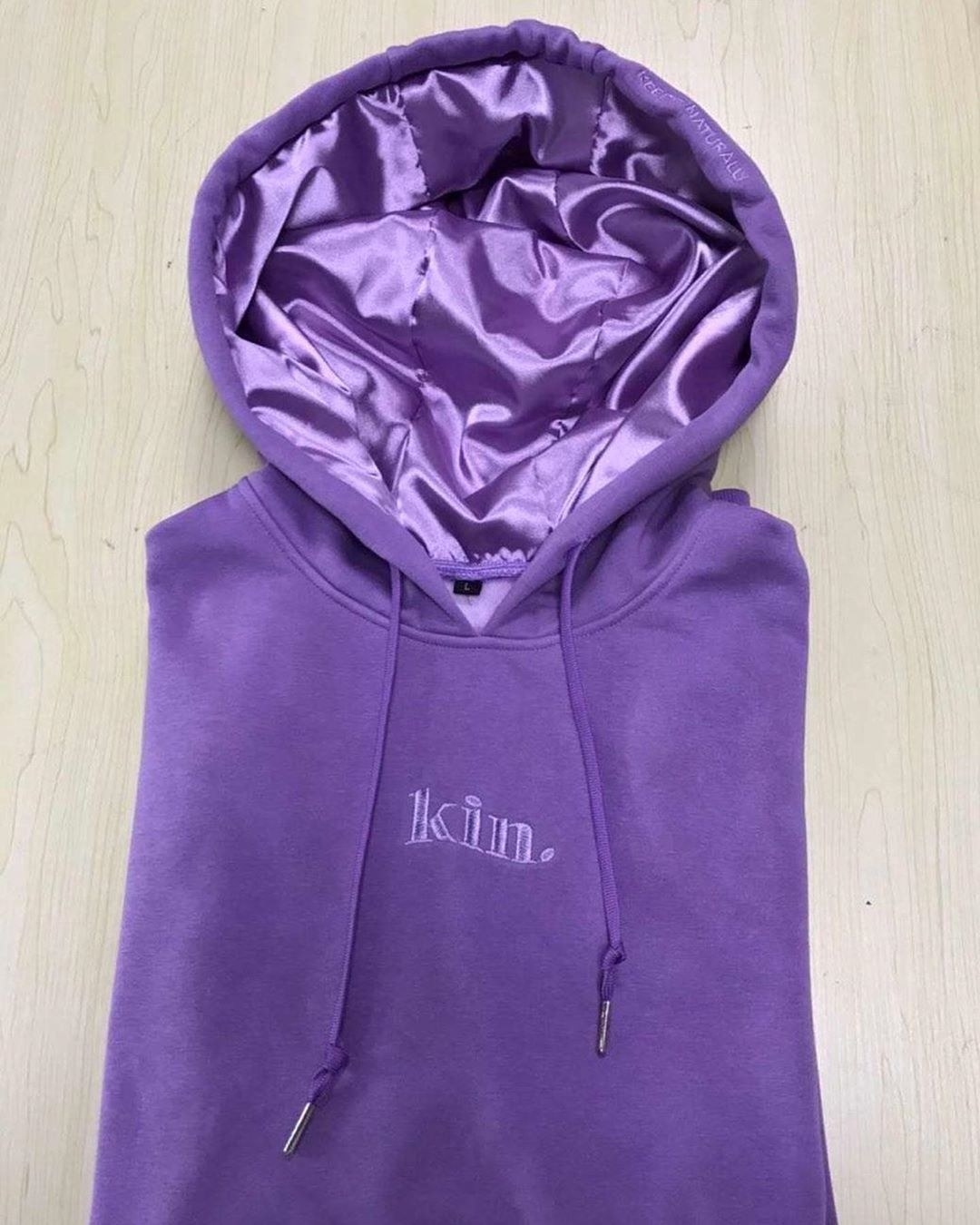 "The hoodie in purple, which says ""kin"" on the front"