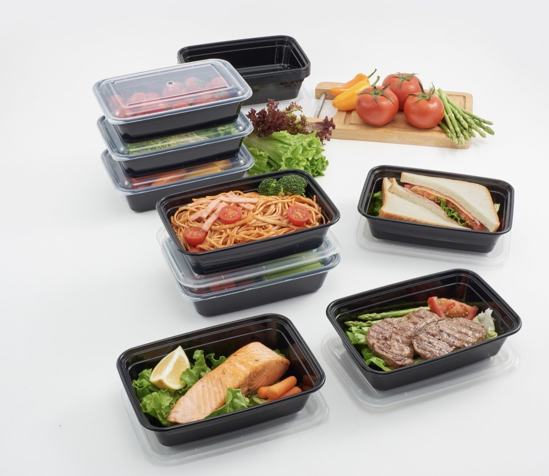 Black meal prep containers with a variety of meals inside several of them