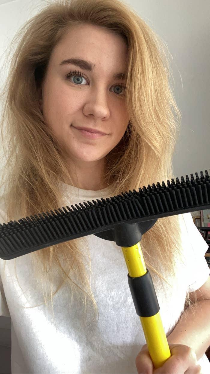 BuzzFeed editor posing with broom