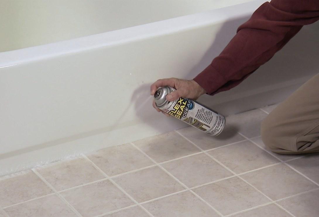 Model is spraying Flex Seal spray onto the outside corner of a bathtub
