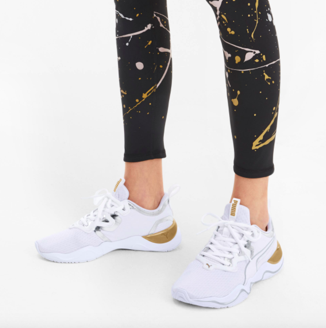 Model wears gold, silver, and white Puma trainers with metallic splatter leggings