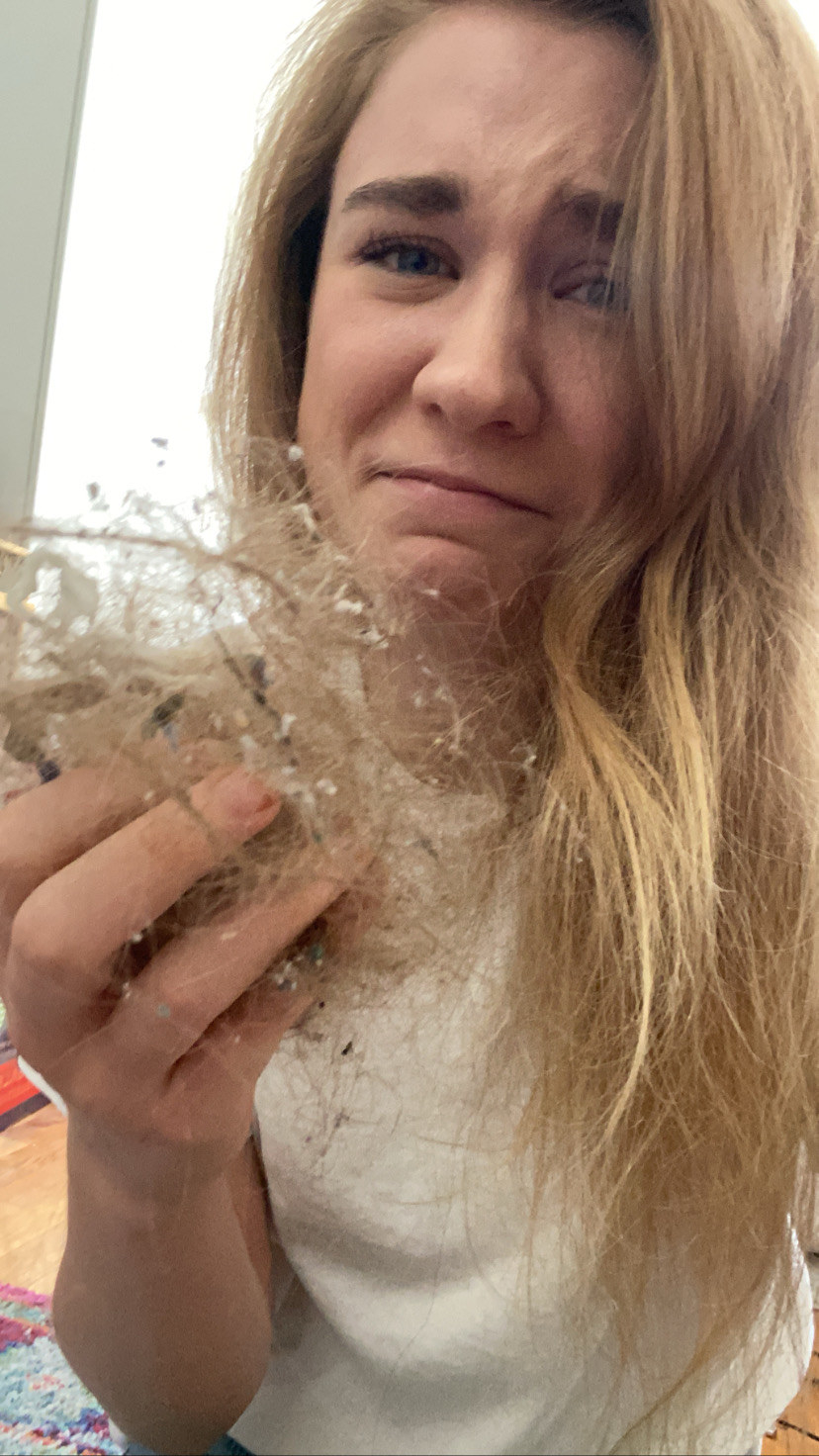 A BuzzFeed editor cringing while holding a gob of their own hair from the floor