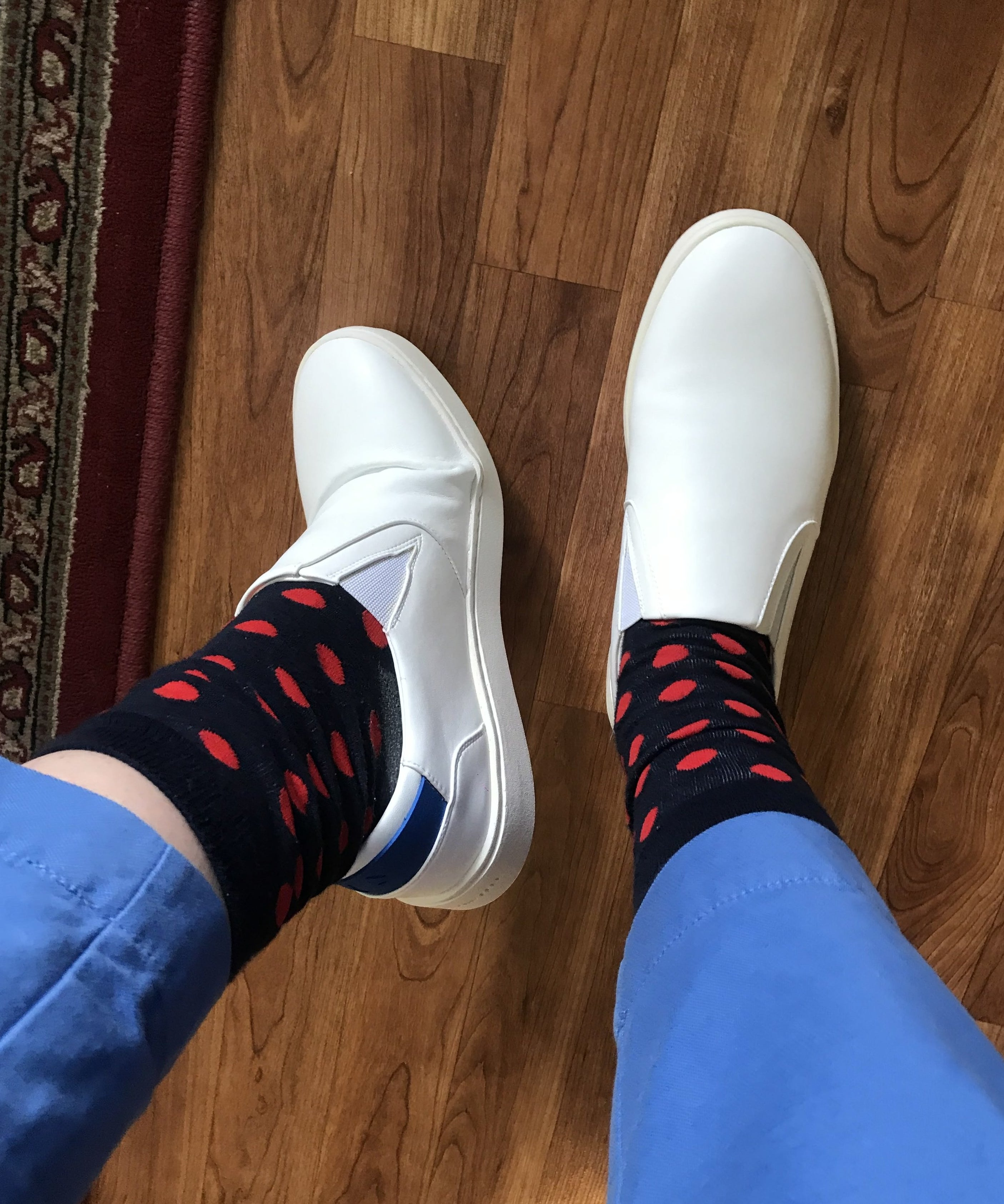 writer's crisp white slip-ons with blue detail on the heel, paired with blue and red polkadot socks