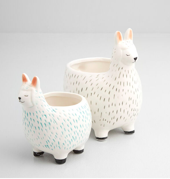 A pair of llama-shaped ceramic planters on a simple background