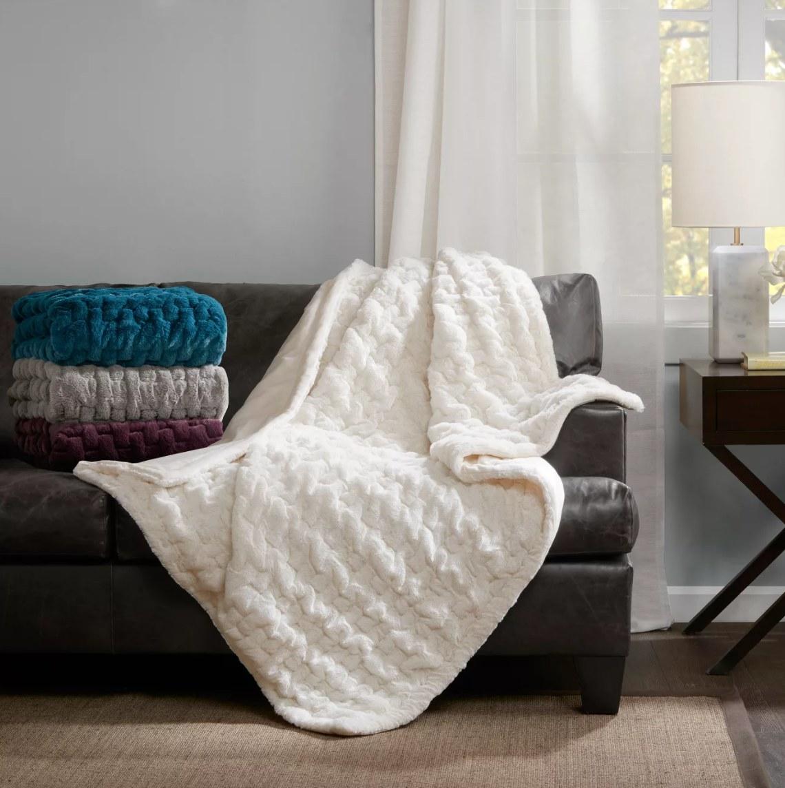 A white faux fur blanket laying across a sofa