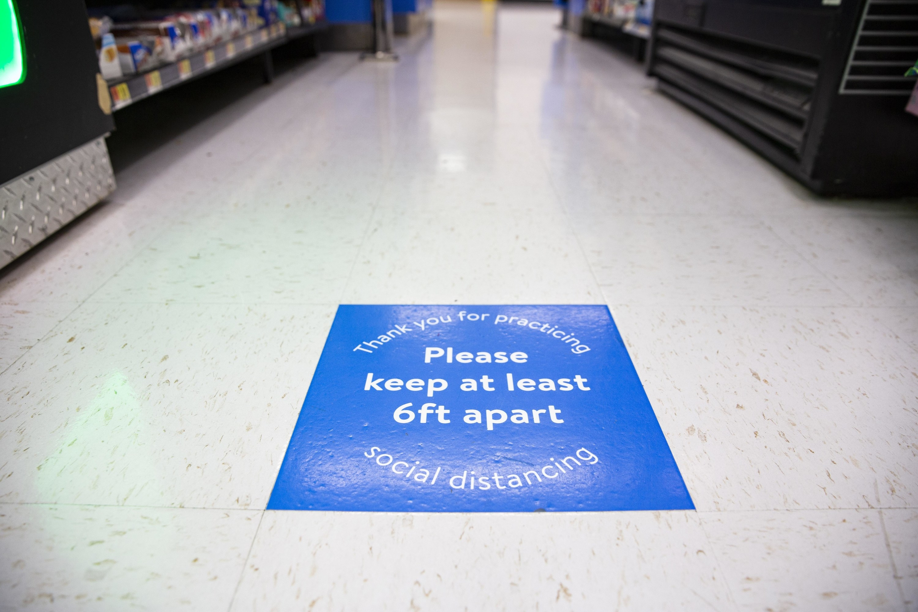 Blue floor sticker reminding customers to social distance and keep at least six feet apart