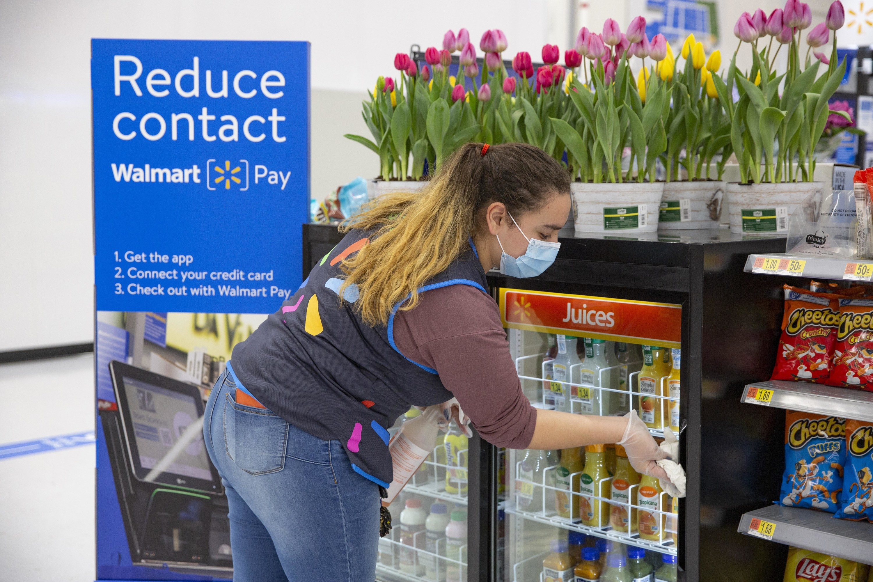 Walmart employee near a cash register and a contacless pay sign