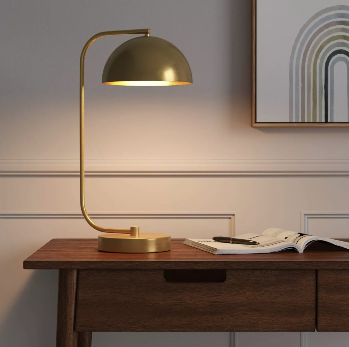 A brass-colored table lamp with a round shade