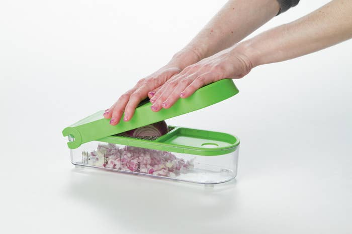 Hands cutting onion with the tool