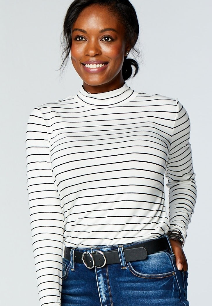 model wearing white and black striped mockneck top
