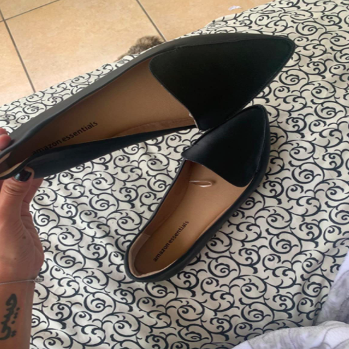 Reviewer holds up same style shoe in a black shade with their hand