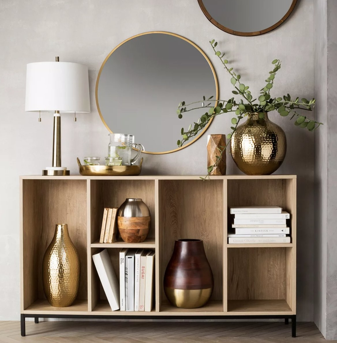 A round wall mirror with thin gold frame