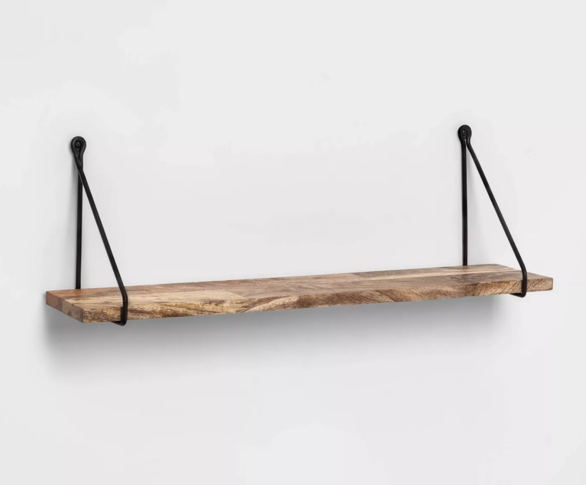 A wooden shelf with black wires for hanging
