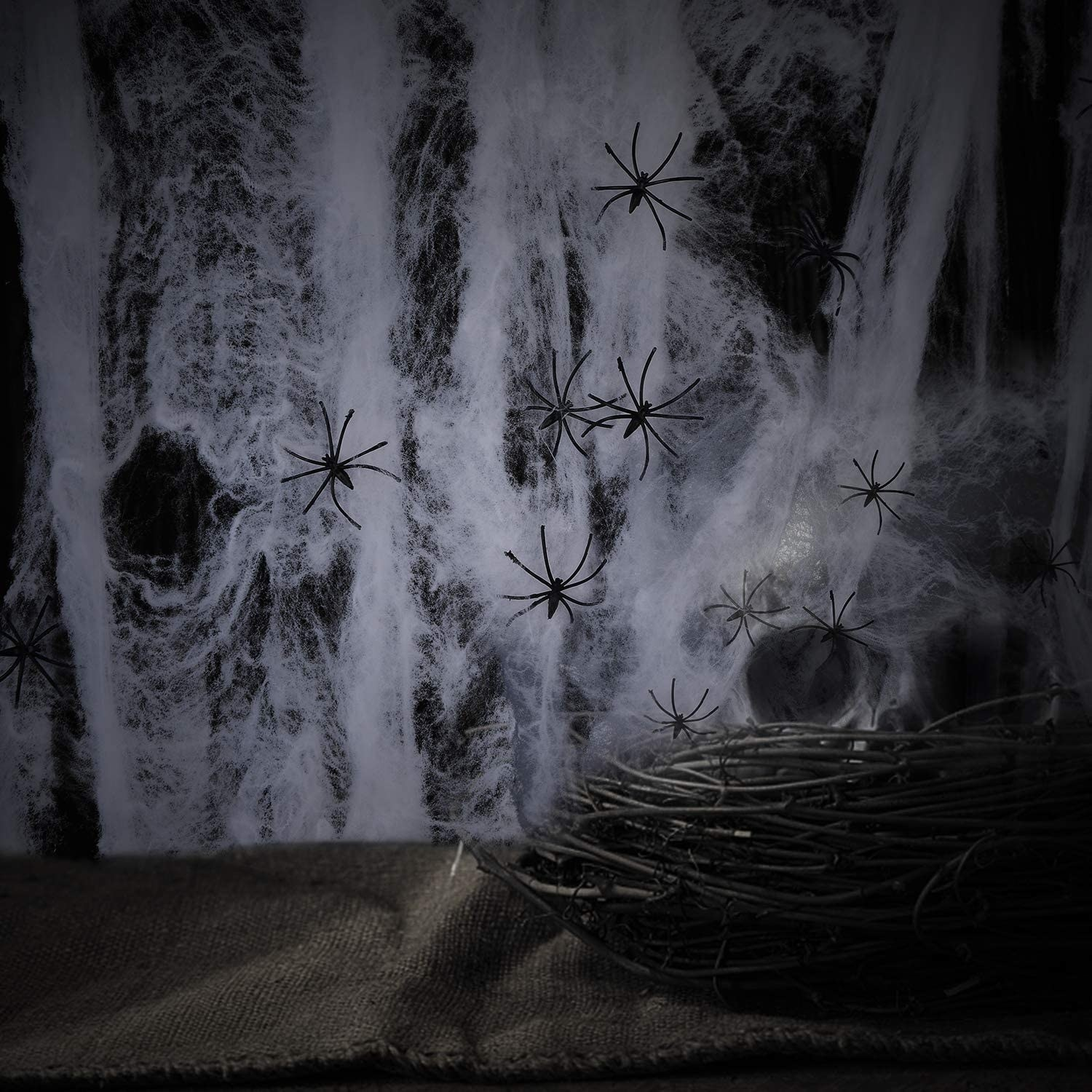 Fake cobwebs are strewn over a wall with fake spiders
