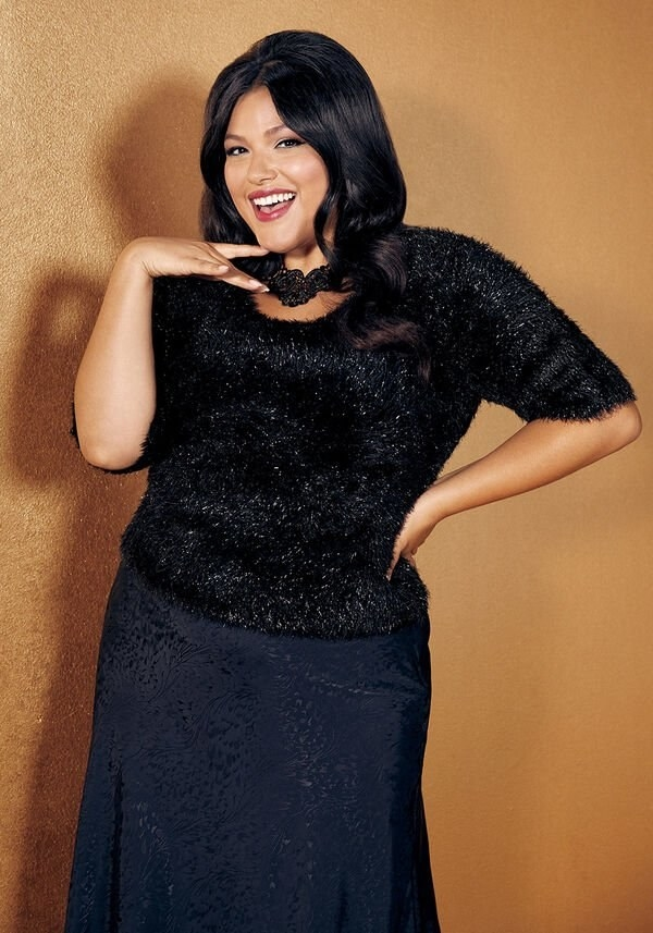 A model wearing the black metallic scoop-neck sweater with a slip skirt
