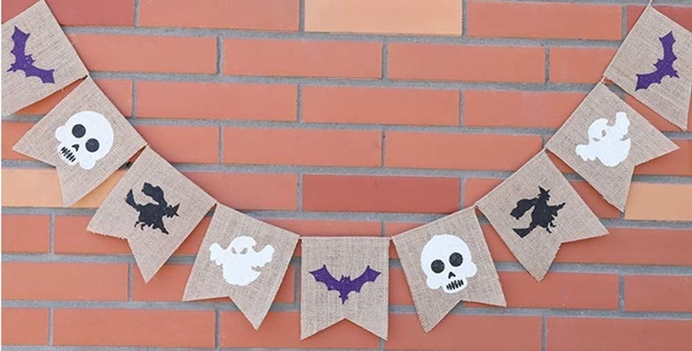 A banner across a brick wall with bats skulls witches and ghosts