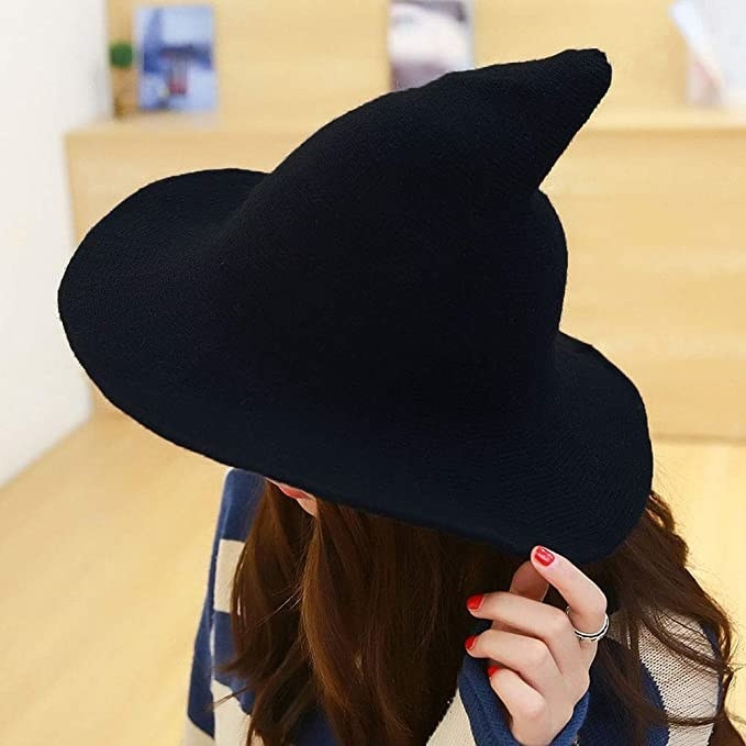 A person wears a black witch hat