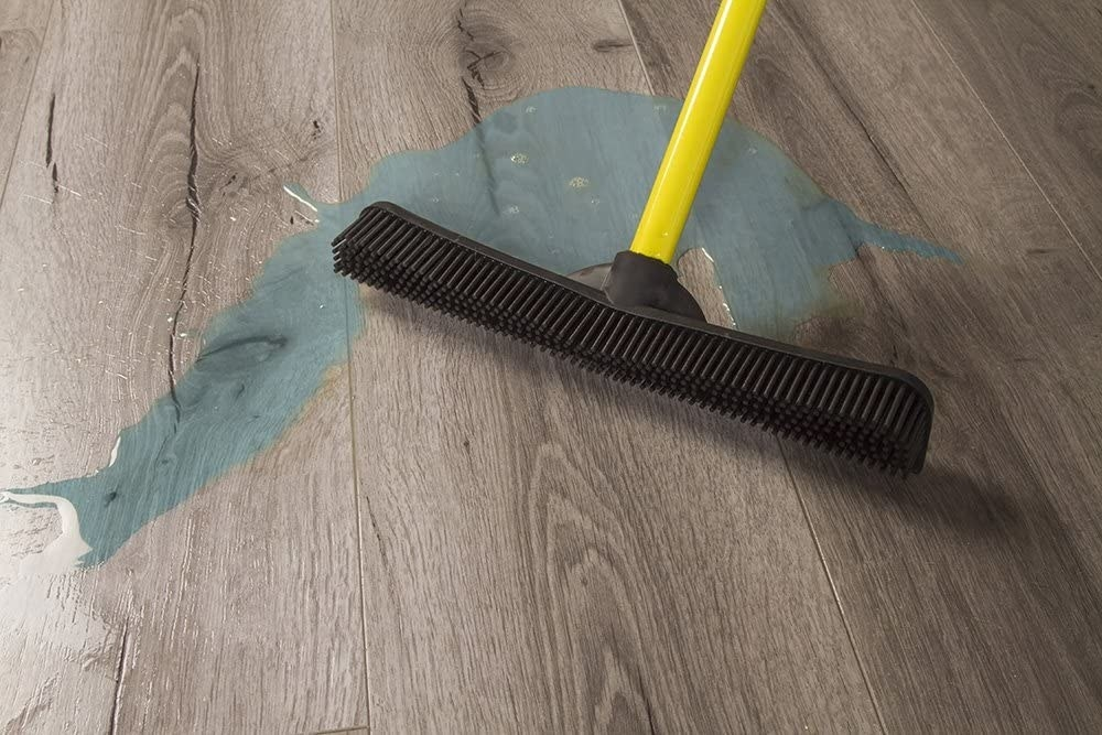 The broom with its edge cleaning up a spill on a hardwood floor