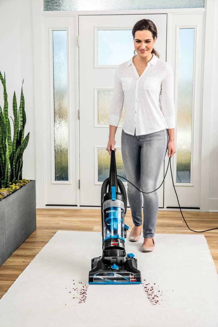 Woman vacuuming crumbs on carpet