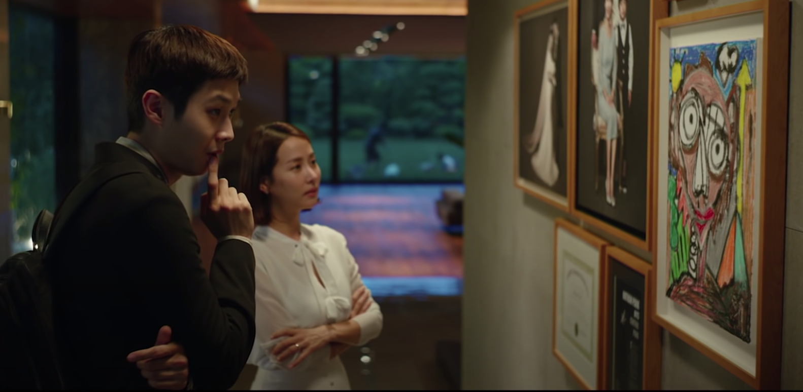 Kim Ki-woo and Choi Yeon-gyo examine art that was done by Yeon-gyo's son