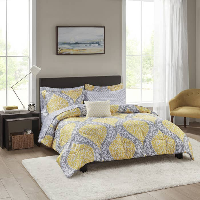 The yellow, grey, and white patterned linens on a queen-size bed