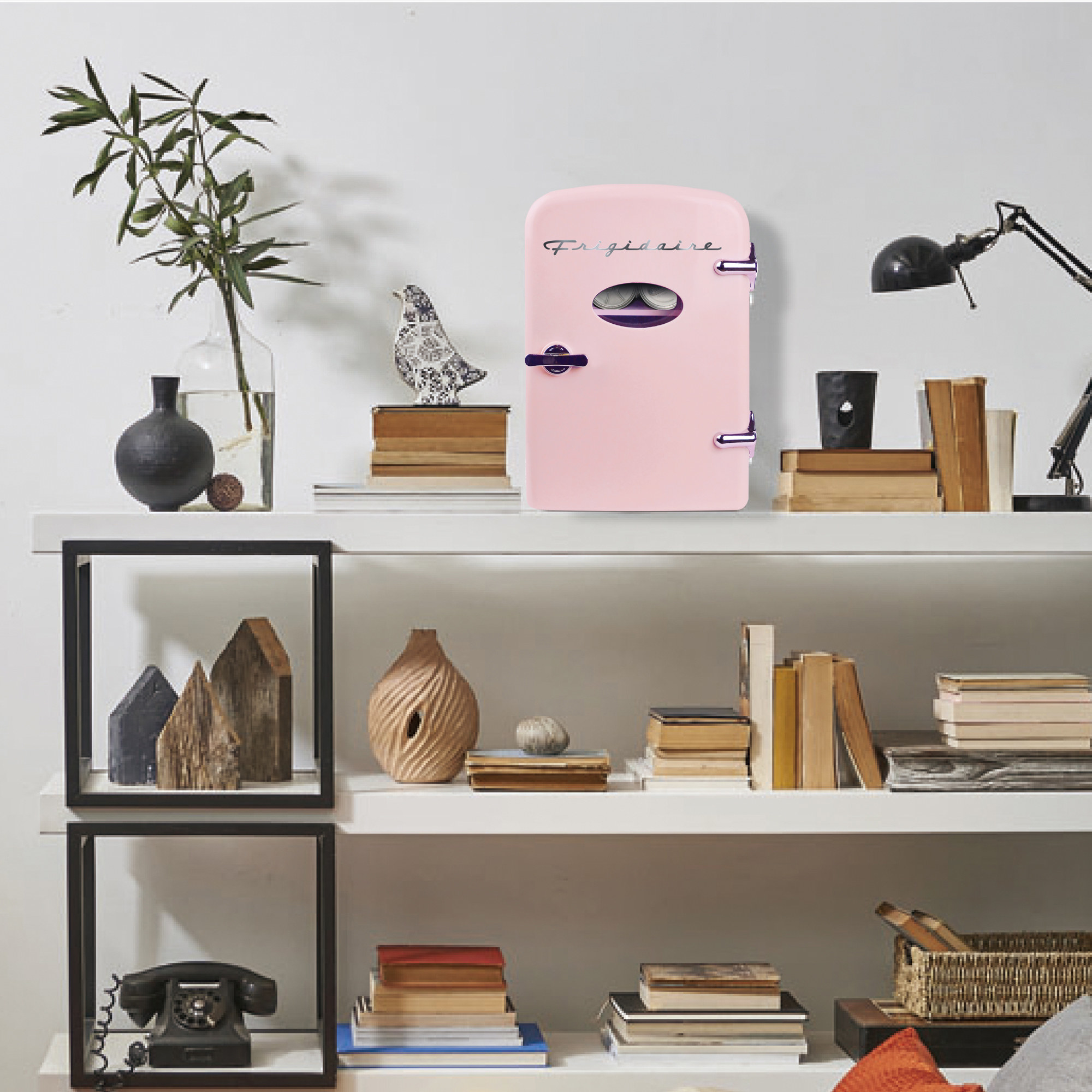 The mini fridge in the color pink on top of a bookshelf
