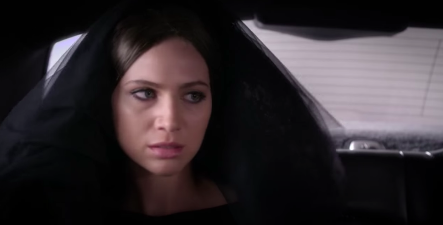 Sara Harvey being revealed as Black Widow in the back of a limo with a black veil on.