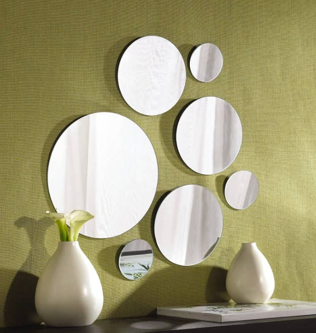 Big and small circle mirrors hang from a green wall above a wooden dresser