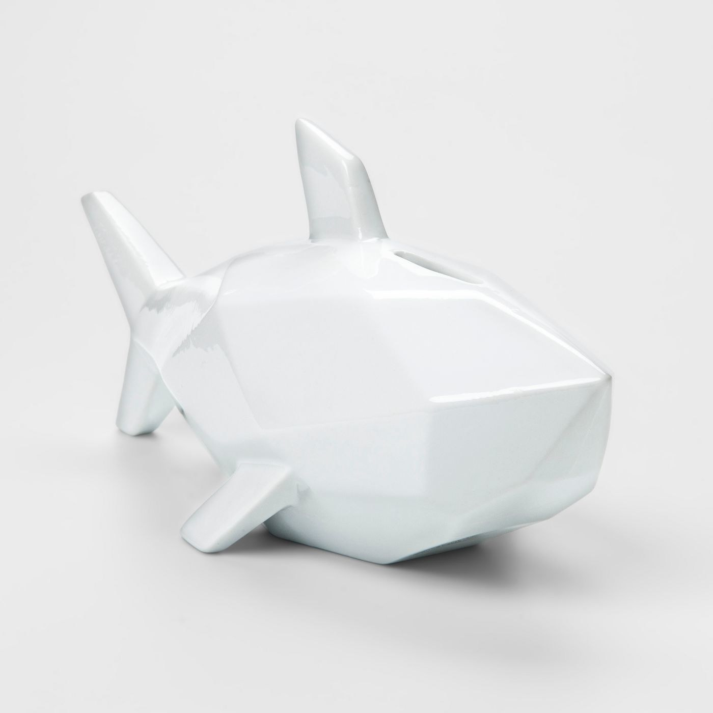 The bank, which is white and shaped like a shark, but abstracted, with many angles and no eyes