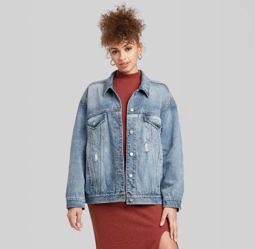 Model wearing loose fit denim jacket over red dress