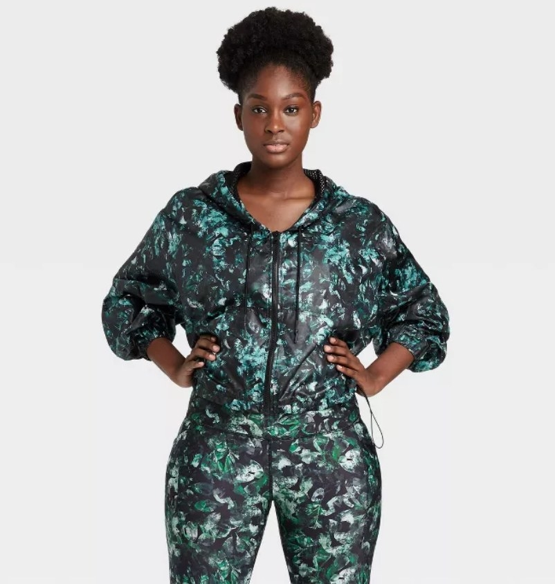 Model wearing green and black floral printed workout jacket