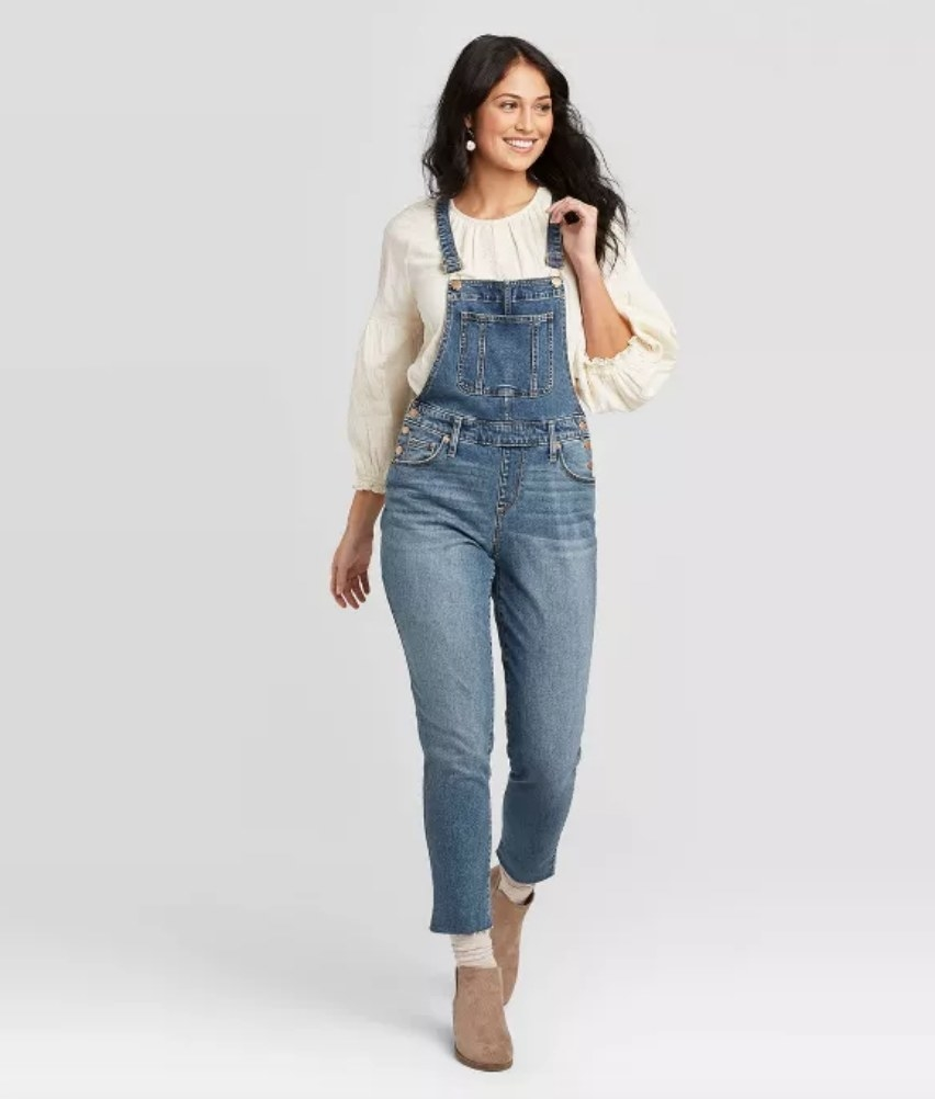 Model wearing denim overalls with off-white long sleeve blouse
