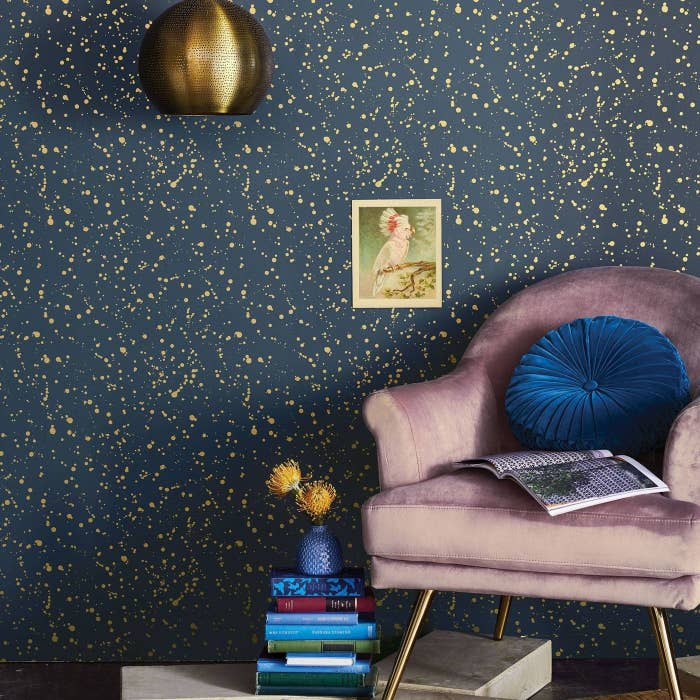 A wall covered in the wallpaper, which is navy blue with a gold splatter effect across it
