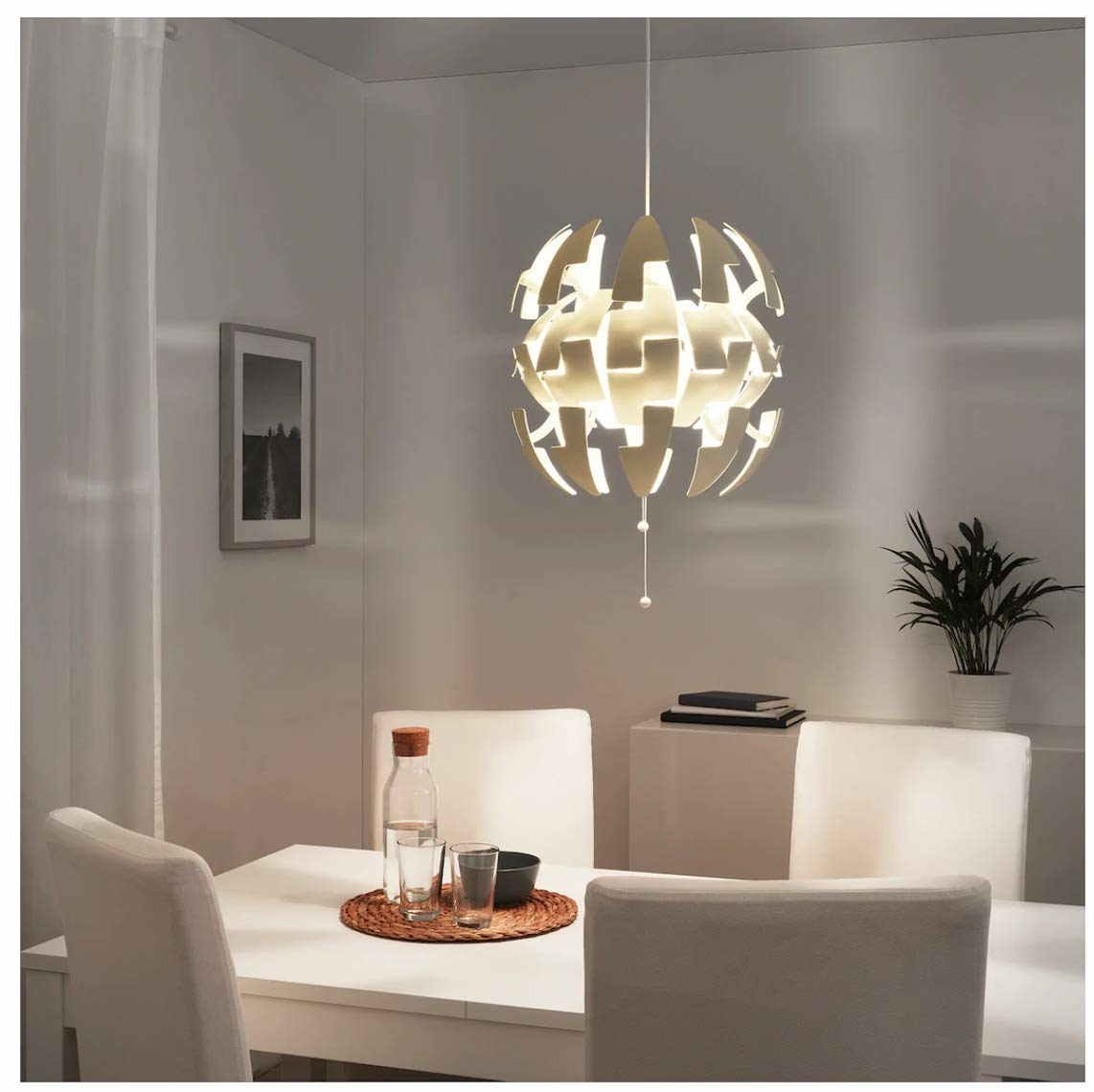 A white pendant lamp over a table