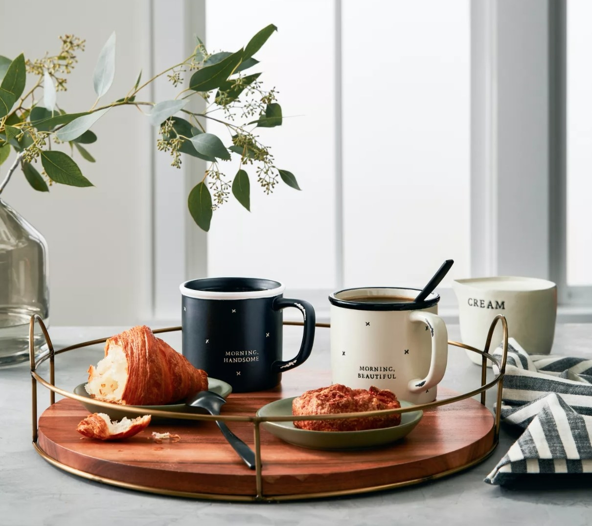 A wooden tray with brass frame and handles, holding breakfast and coffee