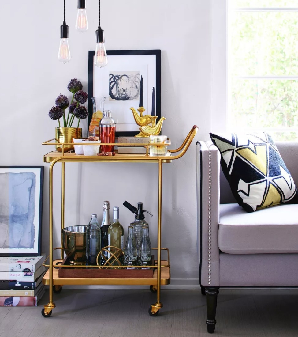 A gold bar cart on wheels with top and lower shelf