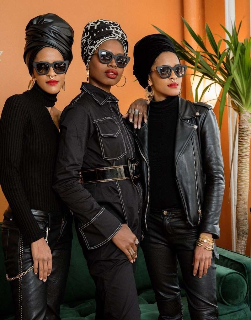 Three models wearing different head wraps: one that's shiny and black, one that has a black and white pattern on it, and one that looks like black velvet