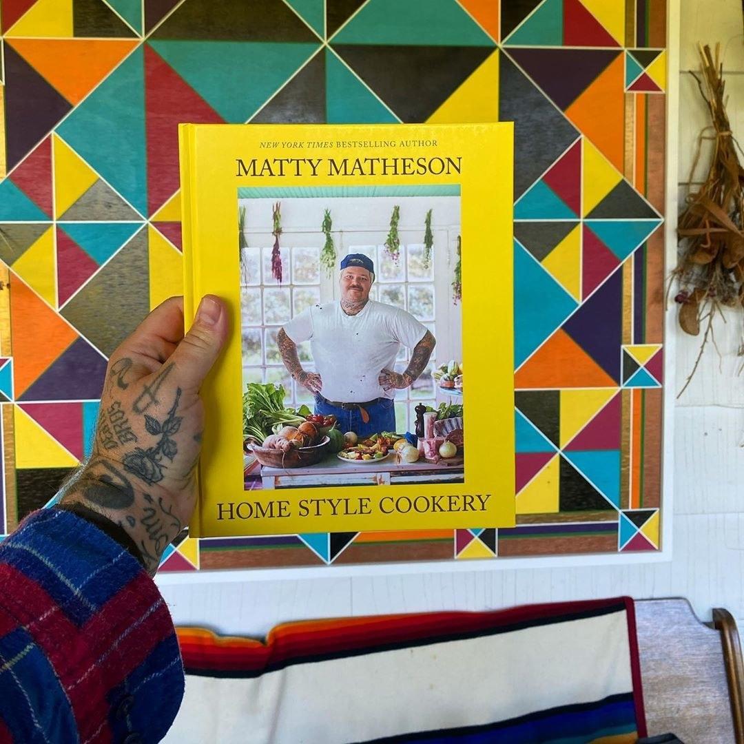Matty Matheson holding up his cookbook
